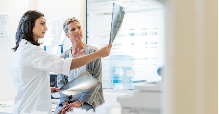 photo d'une femme docteur qui analyse les radiographies d'une patiente qui s'est fait une entorse de cheville