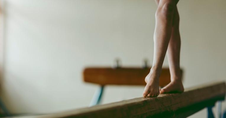 photo d'une gymnastique qui s'entraine à faire des pointes de pied sur une poutre