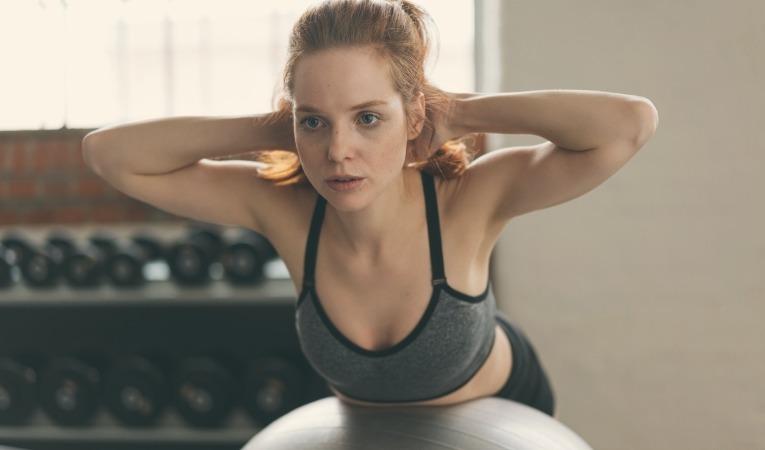 femme allongée sur ballon pratiquant exercice renforcement dos et gainage main derrière la nuque pour soigner névralgie d'arnold