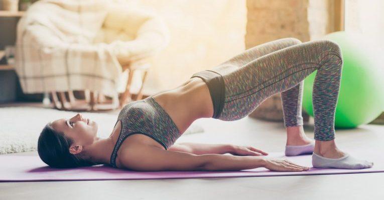 photo d'une femme en tenue de fitness legging qui pratique son sport chez elle et réalise un exercice de pont fessier pour tonifier ses muscles et perdre sa graisse au niveau des fesses