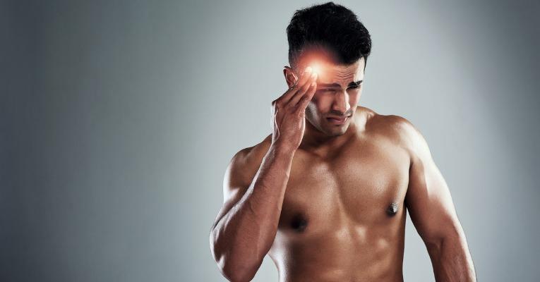 photo d'un jeune homme sportif qui se masse la tempe à cause des douleurs cervicales liés aux combats et entrainements de boxe