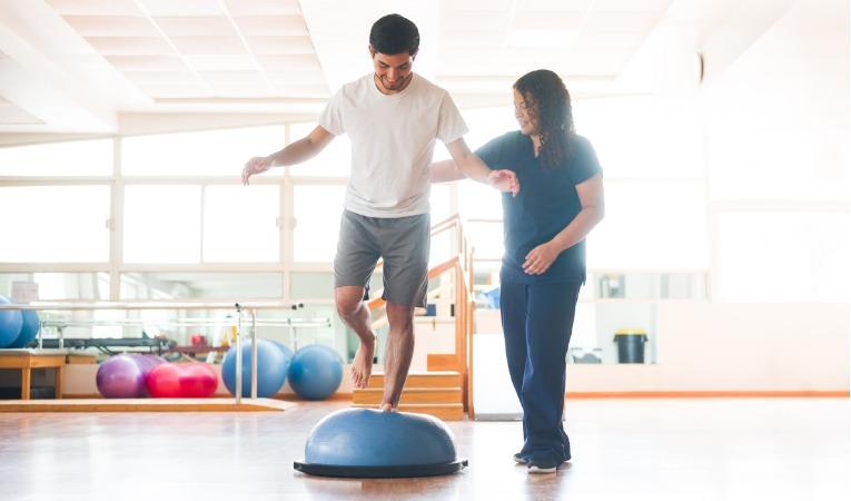 photo d'une jeune kinésithérapeute qui fait travailler l'équilibre d'un jeune homme qui s'est fait une entorse de genou pour lui permettre de reprendre le sport avec une meilleur stabilité