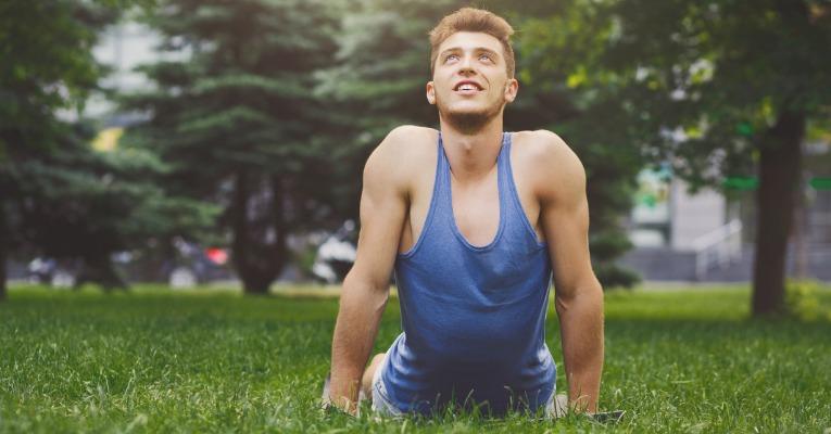 jeune homme dans la nature souriant durant un étirement du dos extension pour douleurs dorsales, dorsalgie