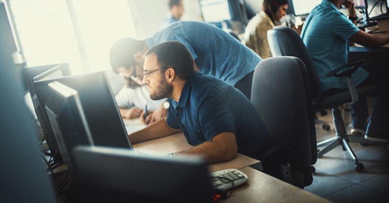 photo d'un jeune développeur qui travail devant son ordinateur dans une mauvaise position et qui risque de souffrir de douleurs à la nuque et de cervicalgie chronique