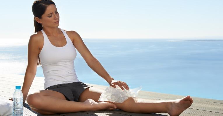 photo d'une jolie jeune femme qui pose un pack de glaçons tout autour de son genou pour soulager ses douleurs d'entorse de genou