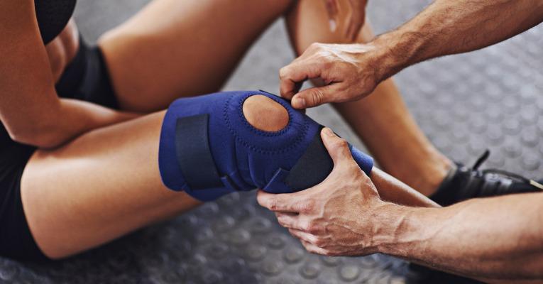 photo d'un kinésithérapeute qui ajuste une genouillère sur le genou d'une jolie jeune femme qui souffre d'une entorse de genou