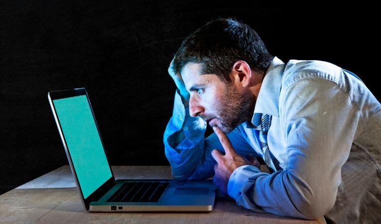 homme assis devant ordinateur mauvaise posture avec risque de douleurs dorsales type dorsalgie