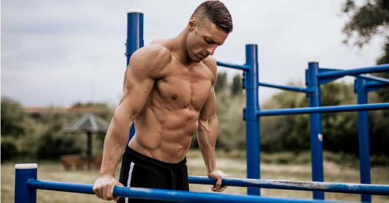 photo d'un homme sportif et très musclé qui réalise une série de plusieurs dips et fait ainsi ressortir ses abdominaux et ses muscles du tronc de manière très visible