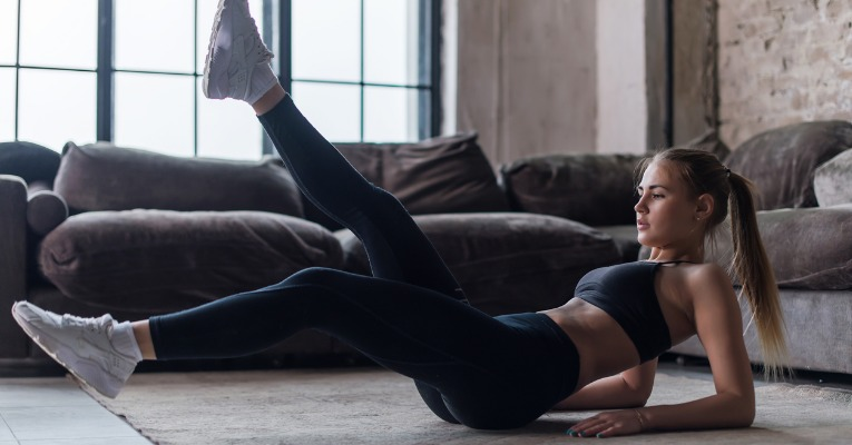photo of a young sportswoman who performs sets of scissors at home to strengthen her abdominals in the most effective way