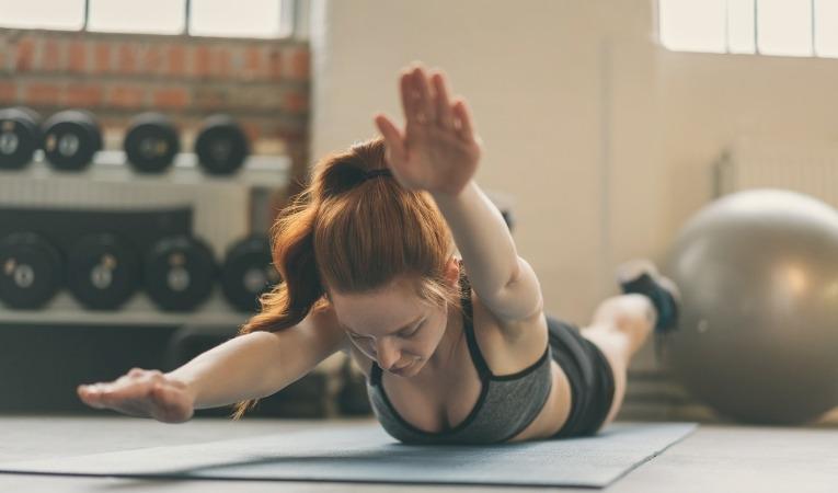jeune femme de face allongée sur tapis de sol dans salle de rééducation pratiquant exercice de renforcement gainage pour lutter contre névralgie d'arnold