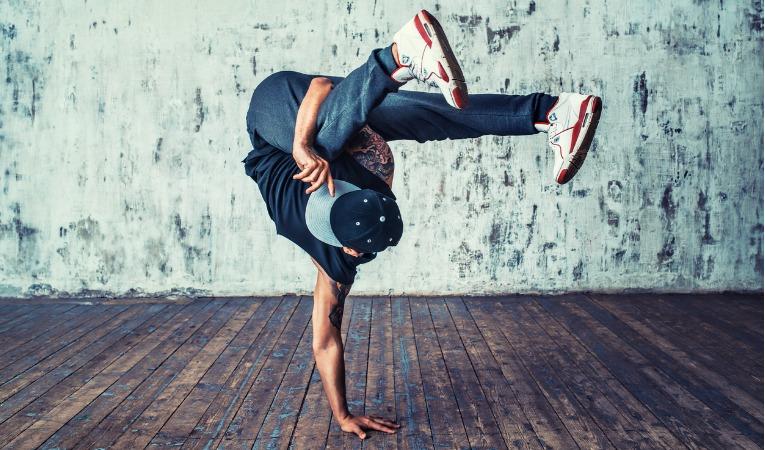 photo d'un jeune homme avec un casquette réalisant une figure de danse hip hop en appui sur un seul bras qui illustre à quel point l'épaule peut être sollicitée de manière très intense après une luxation de l'épaule