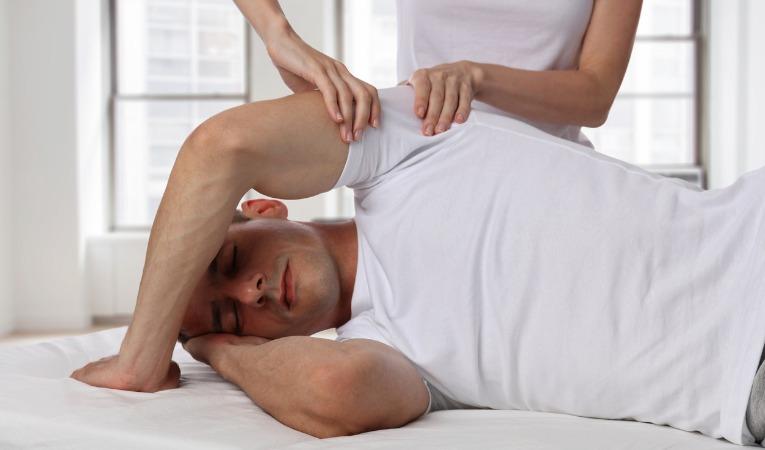 photo de face d'un patient atteint d'une luxation de l'épaule durant une séance de rééducation