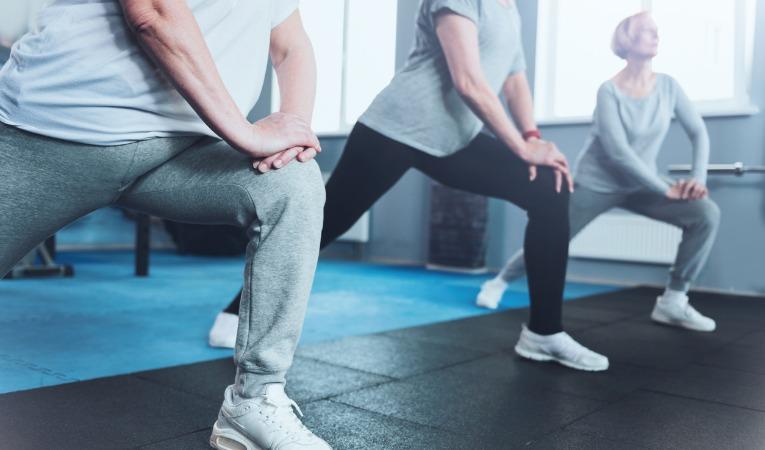 3 personnes pratiquent un exercice de gainage des jambes lors d'une séance de rééducation et de renforcement des jambes après prothèse de genou
