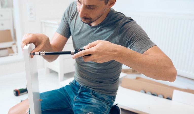 photo d'une homme utilisant un tournevis pour monter un meuble lourd et qui démontre que le bricolage est souvent responsable des douleurs d'une tendinite du coude
