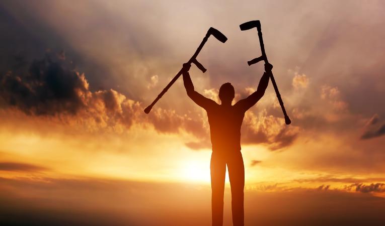 un homme face au soleil est fière de s'être libéré de ses cannes grâce à la rééducation de la prothèse de hanche