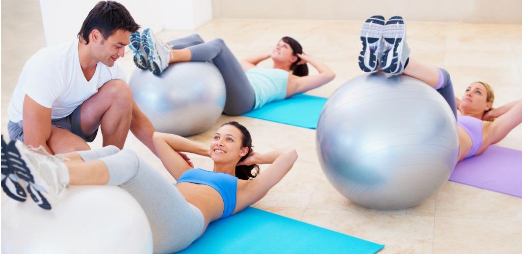 kinésithérapeute coach donne une séance de rééducation à plusieurs femme sur ballon avec exercice de renforcement gainage pour soigner lombalgie chronique