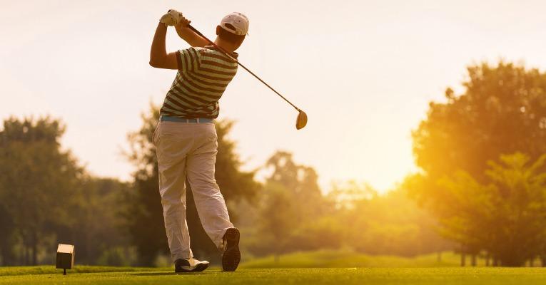 homme de dos qui termine son swing de golf et ressent une douleur interne du coude causée par sa tendinite interne du coude aussi appelée golf elbow