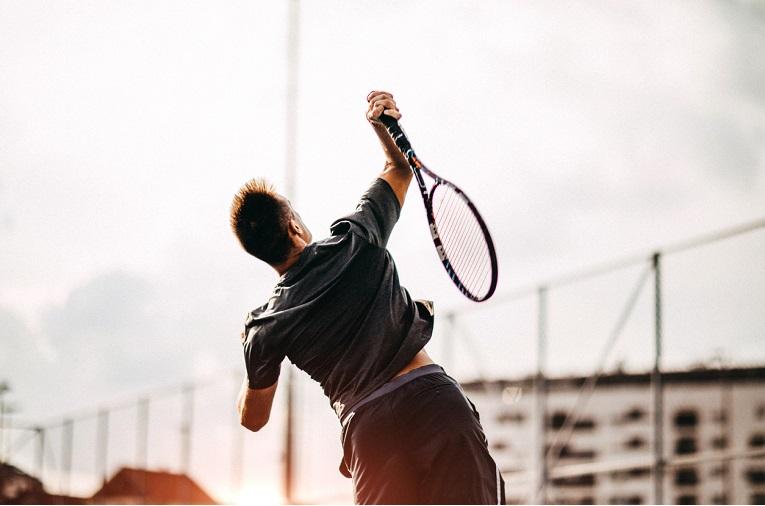 photo de dos d'un joueur de tennis qui réalise un service et montre à quel point ce mouvement est contraignant pour l'épaule et risque de mettre en place des douleurs d'épaule ou des tendinites