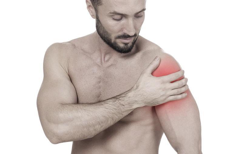 photo d'une jeune homme sportif sur fond blanc qui se tient l'épaule et montre où se situent ses douleurs d'épaule et de tendinite
