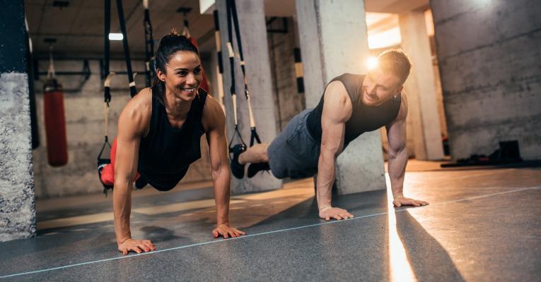 photo d'un couple de jeune sportif qui réalise un exercice de gaine en appui sur les mains et les épaules pour rééduquer leur luxation de l'épaule
